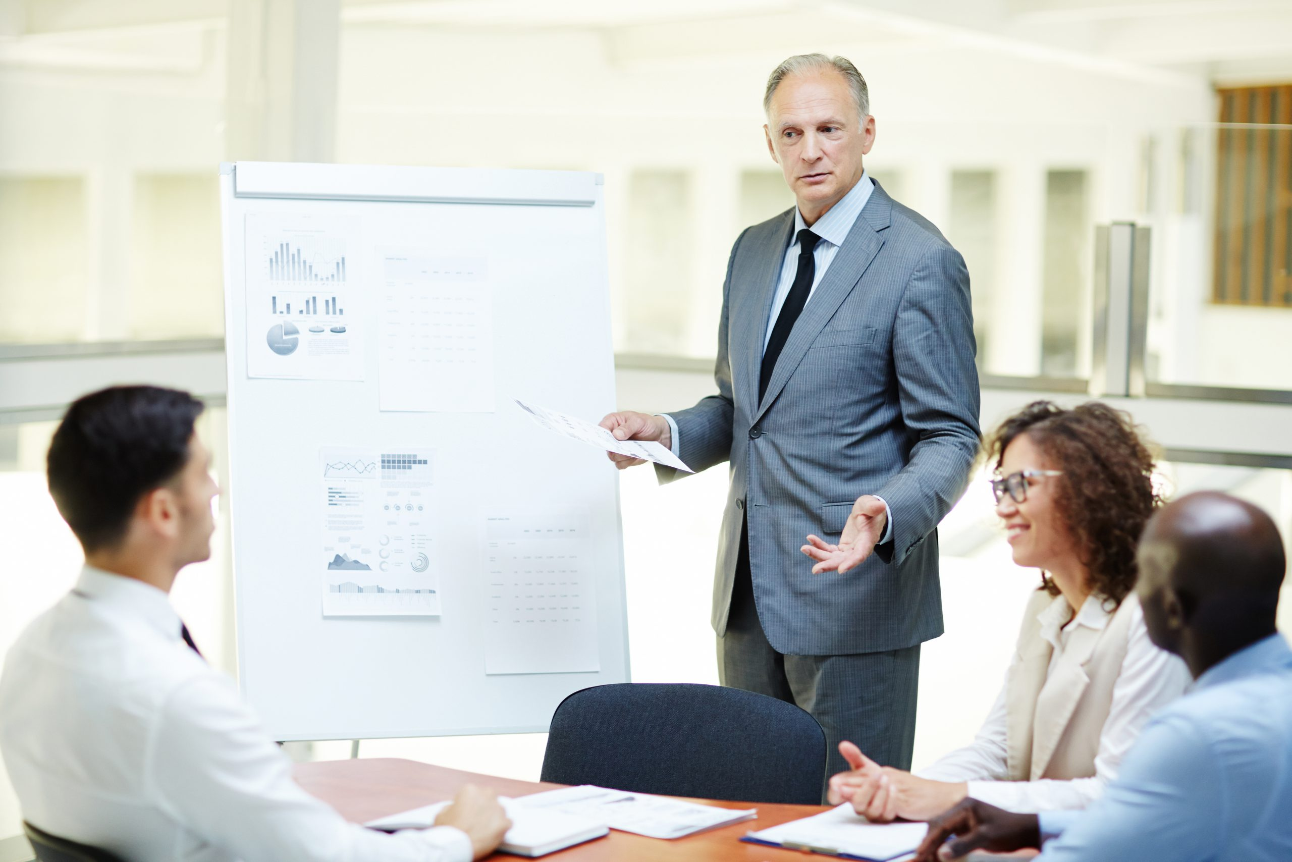 Confident senior trader with paper standing by whiteboard and discussing points of report with colleagues
